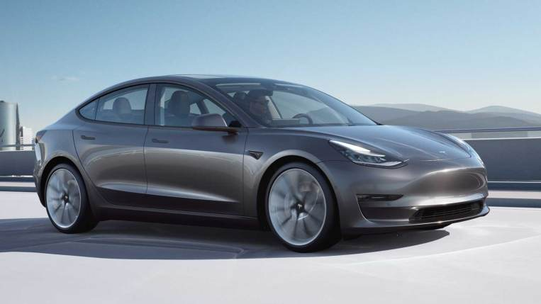 2021 Tesla Model 3 in charcoal, driving.