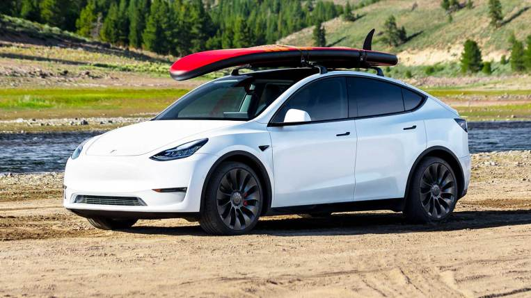 2021 Tesla Model Y in white, with a surfboard on the roof rack.